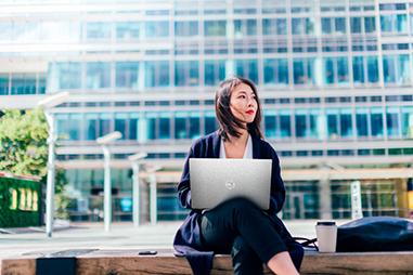 Woman sitting outside using a laptop