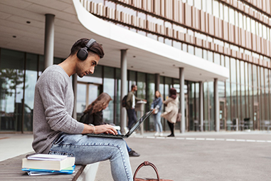 Man sitting outside a building using a laptop and wearing headphones