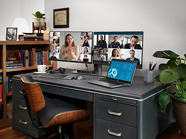 Desk with a laptop and two monitors showing an ongoing video conference.