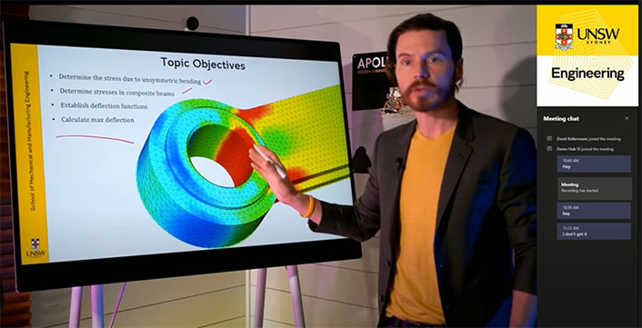 Professor David Kellermann pointing to large screen with 'Topic Objectives' at the top.