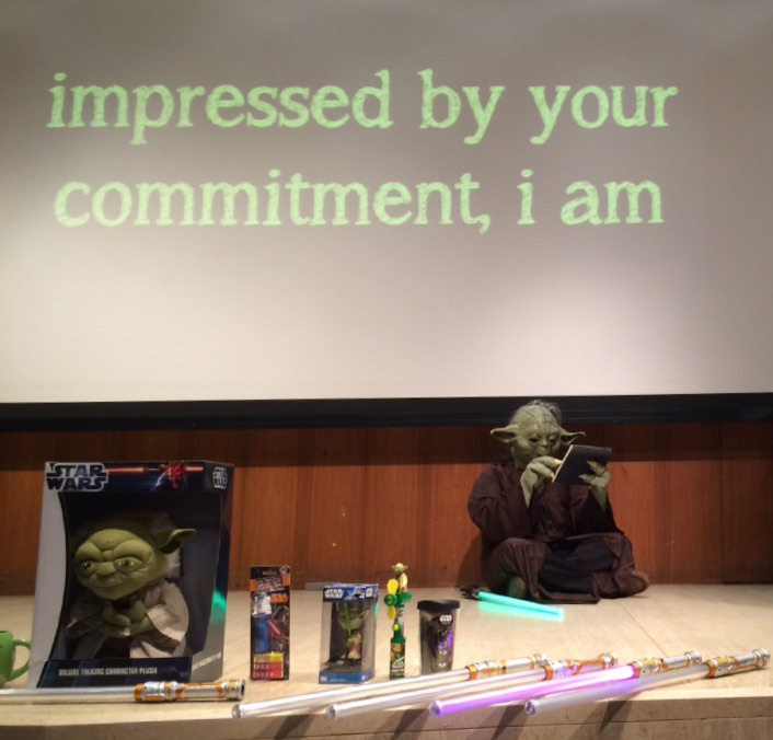 "Person in Yoda costume on stage with various props and screen behind says ""impressed by your commitment, i am"""